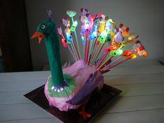 Verjaardags traktatie Iske 4 jaar. Pauw, gemaakt van een steen (buik) met kranten en alufolie. Papier en rietjes met een lampje en lekkers.