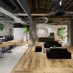 Multi-levelled surfaces of concrete, wood and white gravel define the different working areas within this open-plan Tokyo office by Torafu Architects