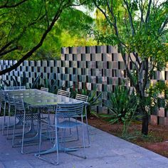 """Steve Martino wove aluminum flashing through rebar uprights like a ribbon, creating a glamorous shimmering privacy wall near the outdoor dining area."" Sunset Magazine"