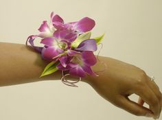 A decorative wire cuff carries a cluster of dendrobium orchid blooms. A lovely prom corsage.