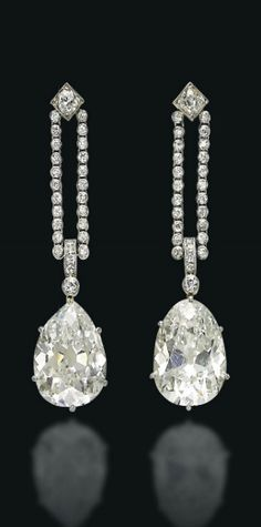 A PAIR OF ART DECO DIAMOND EAR PENDANTS Each suspending an old-cut pear-shaped diamond, weighing approximately 9.46 and 9.43 carats, from a double line of old-cut diamond collets, to a square collet surmount, 1920s, 5.0 cm, in brown leather fitted case