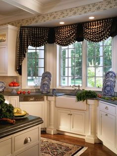 The farmhouse sink in this bright kitchen is flanked by the same columns used on the island and sits into the room's bay window. Details like the checkered valance and plate displays add country charm to the space.