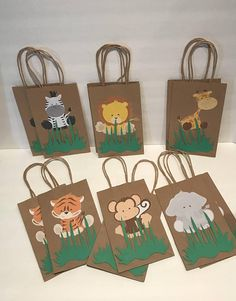 """These adorable Safari favor bags are a special addition to your safari themed party They are great for candy table decoration, and they make special thank you party favor. 12 Goodie Bags (2 of each character) Bags are 8""""H (without handles) X 5"""" W"""