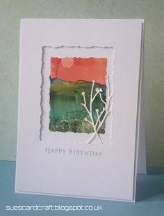handmade birthday card from Sue's Card Craft ... die cut deckle edge frame ... alcohol ink impressionistic landscape on Yupo paper ... used side of a straw to pull the colors across the paper ... wonderful work of art from suescardcraft ...