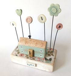Wooden painted house with button and clay flower garden