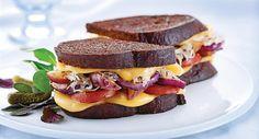 An exquisite offering featuring Wisconsin Edam, knackwurst, and sauerkraut on dark rye bread.
