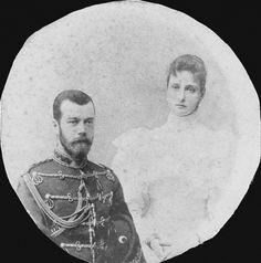 Nicolau II, Imperador da Rússia e Alexandra Feodorovna, imperatriz da Rússia. Nicolau II está à esquerda, vestindo uniforme militar e segurando um chapéu debaixo do braço esquerdo. Alexandra Feodorovna está à direita usando um vestido claro. A fotografia foi cortada num círculo. Cerca de 1894.