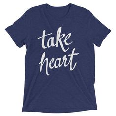 """Tri-blend Take Heart T-Shirt - Inspirational Apparel from 7th & Palm. Inspired by learning to persevere through difficult personal experiences, these illustrated prints are a strong visual reminder of hope and faith. This white """"take heart"""" print uses a handwritten script by artist Andrea Smith, reminding us to rest in the peace only God can provide.  """"...in this world you will have trouble. But take heart! I have overcome the world."""" - John 16:33"""