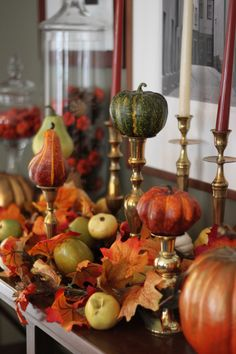 I like the idea of using miniature pumpkins and gourds on candlesticks.