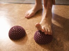 A woman rolling her foot on a stretching ball. HEALTHY FEET-FOR FOOT CRAMPS