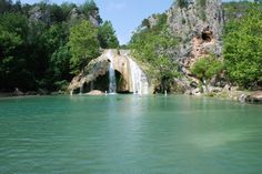 Tucked away alongside the Arbuckle Mountains, the historic Turner Falls Park boasts a natural swimming pool that's formed by Honey Creek rushing down a 77-foot drop.