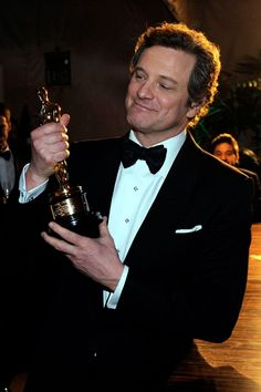 Colin Firth backstage proudly holding his Best Actor Oscar for 'The King's Speech' in 2011.