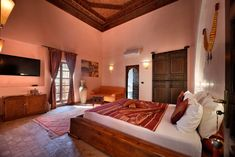 Charming and spacious suite in orange tones with a large bathroom with a shower and elegant decorations. An ancient traditional painted wooden ceiling.  Separate toilets, shower and floor in light brown zellige, safe and minibar, satellite TV, free wifi, air conditioning  #riadlesammonites  Marrakech