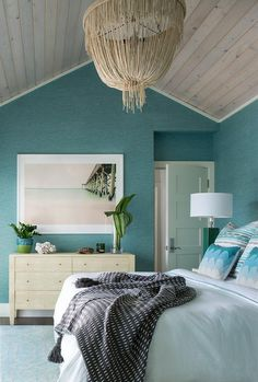 Stunning blue beach style bedroom is clad in ocean blue grasscloth wallpaper complemented with a gray wash vaulted ceiling holding a cream fringe chandelier over a bed dressed in white bedding topped with white and blue pillows.
