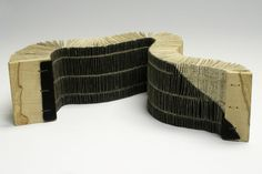 Eclipse, by Susan Porteous..   2007  Recycled book, linen thread, leather, wood..   16½ x 3½ x 2¼ inches    An experimental book in which the pages get progressively wider along its length. It is bound onto a strip of leather that covers all but one corner of the spine and front cover.
