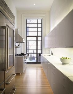 An Elegant Mix - Built within a traditional Brooklyn brownstone, modern cabinets render this kitchen fresh and unexpected. A mix of materials, including wood floors, solid surface cabinets, marble tiles and countertops, and stainless steel appliances, add interest to the long space.