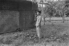 Een Indonesische man spreekt door een microfoon in een kampong. Voor hem een traditioneel huis. Karawang. 1947