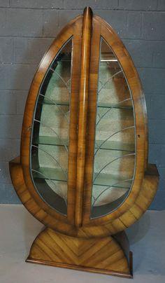 Einnert durch seine abgerundeten, eleganten Formen an ein Blatt: Ein extravaganter Glasschrank aus Walnussholz.