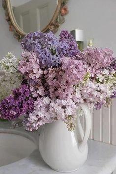 White pink and purple lilacs in a white pitcher vase floral arrangement. Easy diy garden arrangement