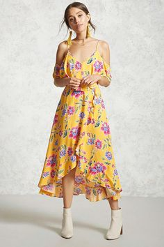 A woven maxi dress featuring an allover floral print, a flounce layer, open shoulders, a V-neckline,  adjustable cami straps, a tulip hem, and a ruffle trim.