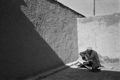 abbas(1944- ), afghanistan. kabul region. city of kabul. an old man reads from the koran in his courtyard. 1986.