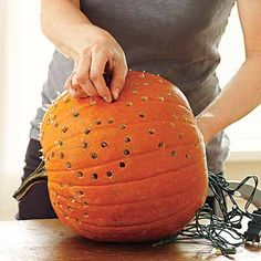 drilling designs into pumpkins nad lighting them with strings of christmas lights
