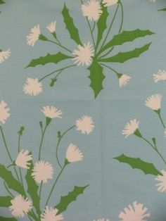 Outstanding 100% Cotton floral pattern on a soft blue background with accents in green and white.