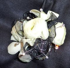 All Seasons Floral- Stunning sparkle black wrist corsage with white ranunculus and orchids.