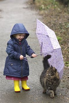 Emily and Waffle share an umbrella outside in the drizzling rain. It's good to see children not afraid to be out in the weather.  ~~  Houston Foodlovers