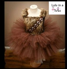 Welcome to my shop. My Chewbacca inspired tutu dress is my take on the very popular Star Wars character. The dress is made up of 3 layers of plain brown tulle. The top is made from a super stretchy crochet top. The top features a furry fabric panel on the front. The shoulder straps are adjustable. This listing is for a knee length version but I can also make in an ankle length (see separate listings). The sizing is for an average size child per age. If your child is smaller/bigger tha...