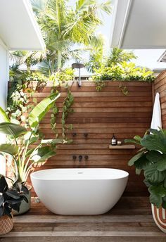 Outdoor bathroom and freestanding bath surrounded by plant outside coastal home #outdoorbath #timberwall #decking #palmtree #coastal #coastalstyle Outdoor Baths, Outdoor Bathrooms, Timber Walls, Timber Flooring, Bath Surround, Urban Kitchen, Bathroom Plants, Plant Wall, Coastal Homes