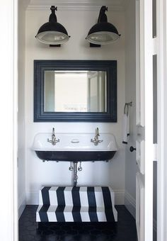 White and black cottage powder room boasts two black industrial pendants illuminating a black beveled mirror placed over a Kohler Brockway Sink fitted with two gooseneck faucets with a black and white striped staircase stool placed atop a black hexagonal floor.