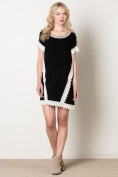 50d87b11f05 Flirty swing dress with embroidered neck line and lace-like crochet  detailing. This dress