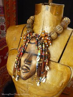 by Helena Nelson-Reed   Necklace; a vintage wooden Dan mask (the Dan peoples live in West Liberia, Guinea Corakry and Ivory Coast) pendant, is combined with vintage trade beads, used cowrie shells taken from an old African textile, contemporary melon cut wood beads, Baltic amber nuggets and other contemporary glass and resin beads.   SOLD