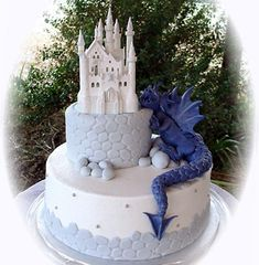 Wedding Cakes Amazing two tier, white and light blue castle wedding cake with a electric blue dragon climbing up the the white castle Dragon Wedding Cake, Castle Wedding Cake, Unique Wedding Cakes, Beautiful Wedding Cakes, Beautiful Cakes, Unique Cakes, Pretty Cakes, Cute Cakes, Awesome Cakes