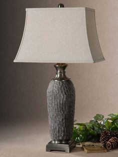 Stone Finish Ceramic Lamp Western  Lamps - Textured ceramic finished in an old stone bronze with a dusty gray wash and heavily antiqued brushed aluminum accents. Rectangle bell shade in oatmeal linen fabric with natural slubbing.