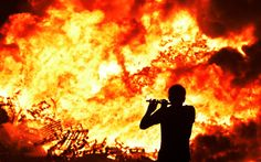 Iain McFarland, an Orange bandsman, plays his flute during the 11th night bonfire at the New Mossley housing estate in Belfast, Northern Ireland   July 2015 Images Of Ireland, Good Riddance, Wtf Moments, Dumpster Fire, Culture War, Pictures Of The Week, Blue Flames, July 17, Cool Photos