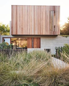 A landscape of native grasses designed by GSLA Studio complements the raw textures of the concrete-and-ipe front facade. #exterior #architecture #modern #landscape #dwell  Photo by @bryceduffy Architecture by @fleetwoodfernandez Location: Los Angeles, California