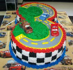 "Cake Idea! I will leave this a 11x15 Marble Sheet Cake. Color frosting Green and Yellow. Leave 1 White and have a Chocolate. Make Road in the shape of a 2 with Chocolate frosting, pipe Yellow lines. Add Green ""grass"" everywhere else on top. Checkered sides with White and Chocolate. Add 2 Cars (Mater and Lightning McQueen). Bradon will have mini 2 shaped cake. Only frost top Chocolate with pipe Yellow lines."