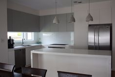 Kitchen - L shaped kitchen with island. Grey and white. Stone bench top.