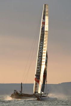 Sir Ben Ainslie's America's Cup wingsail catamaran 'J.P.Morgan BAR' heading across Freshwater Bay at dawn during the J.P. Morgan Asset Management Round the Island Race.