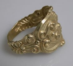 "Ring: ca. 4th-5th B.C.E., Celtic, gold. ""These rings evoke the splendor of the Celts and their love of personal adornment. The upper ring is one of the most lavish surviving examples. The rams' heads are similar to those on the great gold neck ring from Frasnes-lez Buissenal also exhibited in this case. The two smaller rings present a combination of tendril motifs, some echoing symmetrical designs that appear to be abstractions of a face."""