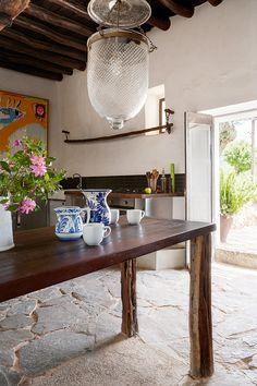 Cocinar - AD España, © Belén imaz En la cocina, mesa de sabina con cerámica popular y, al fondo, pintura de Jesús de Miguel.