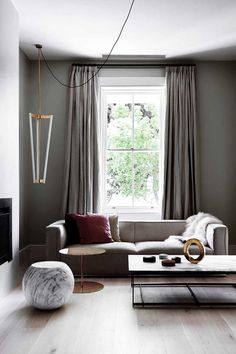 Gray living room with neutral sofa and pops of raspberry