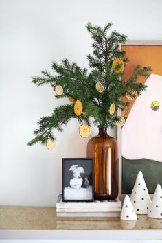 evergreen branches in a large apothecary bottle with citrus ornaments