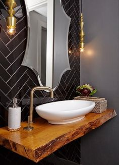 Chic contemporary powder room showcases a stunning live edge floating vanity finished with an oval vessel sink with a brass faucet fixed to the side of the sink beneath a beveled vanity mirror lit by brass light pendants mounted on black herringbone wall tiles.