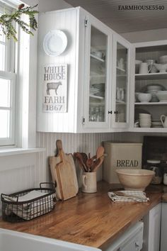 White plate + sign on cabinet by sink // bread box // cutting boards // open cabinets