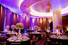 Ballroom wedding reception with tall centerpieces in ivory and light pink and modern lighting
