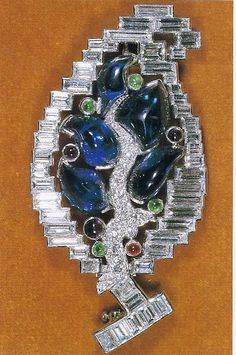 Queen Elizabeth The Queen Mother's Leaf Brooch - Framed in diamond baguettes, this Cartier leaf-shaped brooch has a pave-set diamond veigh down the centre, and is set with irregularly shaped Indian-cut Ceylonese cabochon sapphires, and small round emeralds, amethysts and a ruby.