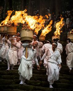 Parade of fire by Hidetoshi Ogata - Ogi-Matsuri is one of the largest fire festivals in Japan and is held in Kumano mountains of Wakayama Prefecture on July 14 every year. The god of the waterfall, which is enshrined in Kumano Nachi Taisha, comes back to Hiro-shrine (Nachi Falls) once a year in this festival. The most impressive scene in this festival is that men wearing white clothing carry a large fire torches which weigh about 50 kg
